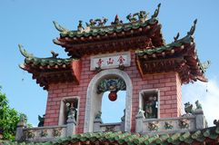 A colourful brick arch marks the entrance to a Vietnamese temple. Stock Photo