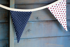 Colourful bunting. Brightly coloured bunting against wooden wall Royalty Free Stock Images