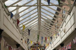 Colourful bunting flags in a glass rooved walkway. Multi-coloured bunting flags and English flags in a glass rooved shopping centre, walkway in an English town Stock Photography