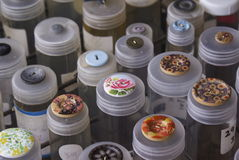 Colourful Buttons. Brightly coloured fashion buttons for sewing, needlework or dressmaking in tubes at a market stall. The colour mixes were and range of button Stock Image