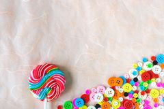 Colourful buttons and swirl lollipop on pink mulberry paper. Idea for background royalty free stock photo