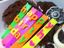 Colourful candles on Chocolate cake and biscuit on white background Royalty Free Stock Image