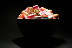 Colourful Candy. Candy in a rim lit white bowl agaqinst a black background Stock Photos