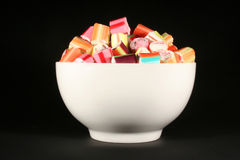 Colourful Candy. White bowl filled with candy against a black background Stock Photos