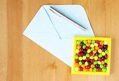 Colourful candy frame, open blue envelop and pen on the table. Copy space. Flat lay. Top view Royalty Free Stock Image