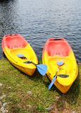 Colourful canoes. Two colourful canoes sitting on the shore Royalty Free Stock Photography