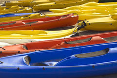 Colourful canoes lie in two rows. Bright yellow, red and blue canoes lie in two rows on sandy beach Stock Photos