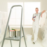 Colourful cans of paint on a stepladder young decorator smiling Stock Photography
