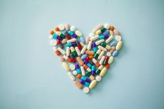 Colourful capsules medicine in heart shape Royalty Free Stock Photos