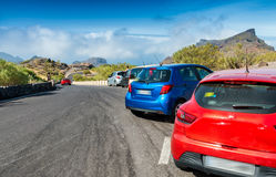 Colourful cars parked on a mountain road Royalty Free Stock Photo