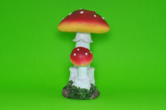 Colourful ceramic mushroom isolated in green background. Equipped with artificial grass Royalty Free Stock Images