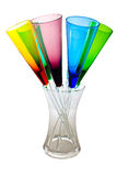 Colourful Champagne Flutes. Unusual glass multicoloured champagne flutes in a clear glass container on an isolated white background Royalty Free Stock Image