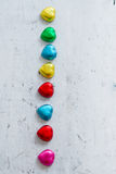 Colourful chocolate hearts on wood Stock Images