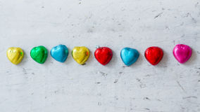 Colourful chocolate hearts on wood Royalty Free Stock Images