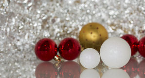 Colourful christmas baubles against a bokeh background. Colourful christmas baubles against a silver bokeh background Royalty Free Stock Photos