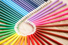Colourful circle of wooden pencils on brown background, wooden table royalty free stock image