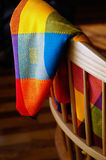 Colourful Cloth. Mexican cloth woven from vibrantly coloured fibers draped over the back of a chair Royalty Free Stock Photo
