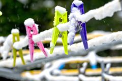 Colourful Clothes Pegs in Snow. Colourful clothes pegs hanging on a rotary washing line in the snow Stock Images