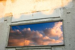Colourful clouds reflected in a window on an old white brick wall stock image