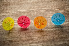 Colourful cocktail umbrellas lying on a wooden Stock Photos