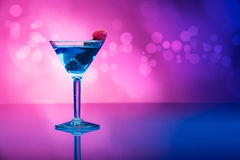 Colourful cocktails garnished with berries, background with light effects. Blue and purple tone royalty free stock image