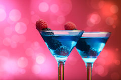 Colourful cocktails garnished with berries, background with light effects Stock Photo