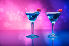 Colourful cocktails garnished with berries, background with light effects Royalty Free Stock Image