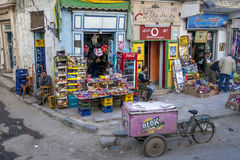 A colourful corner shop in a street of Giza in Cairo, Egypt. Men sit outside a colourful corner shop in a street of Giza in Cairo, Egypt stock image