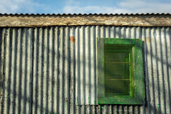 Colourful corrugated iron wall,window and blue sky. Contrasty detailed scene with corrugated iron wall and window with shadows on it against blue sky Stock Photo