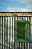 Colourful corrugated iron wall,window and blue sky. Contrasty detailed scene with corrugated iron wall and window with shadows on it  against blue sky Stock Photography