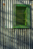 Colourful corrugated iron wall and window. Contrasty detailed scene with corrugated iron wall and window with shadows on it Royalty Free Stock Images