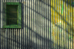 Colourful corrugated iron wall and window. Contrasty detailed scene with corrugated iron wall and window with shadows on it Royalty Free Stock Photo