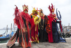 Colourful Costumes. Venice, Italy- February 19th, 2012: Group of people disguised in colorful costumes pose in front of the gondolas dock during the Venice Royalty Free Stock Images