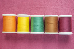 Colourful cotton reel on cotton textile Royalty Free Stock Photo
