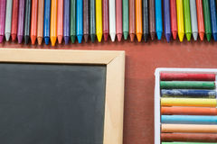 Colourful crayon with book and blackboard Royalty Free Stock Images