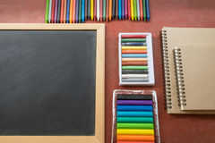 Colourful crayon with book and blackboard Royalty Free Stock Image