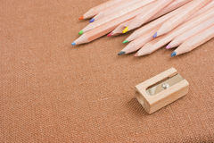 Colourful crayons and pencil sharpener on brown. Stock Image