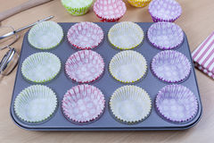 Colourful cupcake liners placed in a baking tray Stock Photo