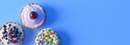 Colourful cupcakes on blue background. Banner Stock Photo
