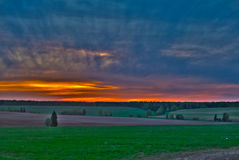 Colourful dawn over fields with unusual clouds Stock Photos