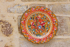 Colourful Decorative Plate. A Hand Painted Ceramic Decorative Plate on a Wall Royalty Free Stock Image