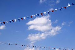 Colourful decorative triangular flags under blue sky with clouds. Festive decoration, festival stock image