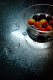Colourful delicious cherry in transparent glass bowl. Red orange yellow white dark pure colour. Fresh cherry covered by half water in transparent glass bowl on Royalty Free Stock Photo