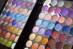 Colourful display of eye make-up. In an open portable compact with eye shadow in all the colours of the spectrum, also reflected back in the mirror in the lid Royalty Free Stock Photo