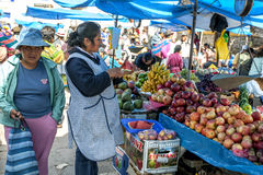 A colourful display of fruit at Pisac in Peru. A fruit seller cuts a piece of watermelon at the market in Pisac in the Sacred Valley of the Incas in Peru stock images
