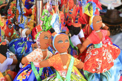 Colourful Dolls, Oranjestad, Aruba. A display of colourful dolls and in the background colourful hand bags. One of the dolls has a pink dress, another a yellow Stock Image