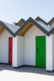 Colourful doors of green and red, with each one being numbered individually, of white beach houses on a sunny day Stock Images