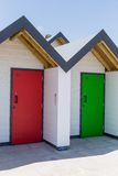 Colourful doors of red and green, with each one being numbered individually, of white beach houses on a sunny day Stock Photo