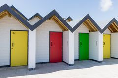 Colourful doors of yellow, green and red, with each one being numbered individually, of white beach houses on a sunny day Royalty Free Stock Image