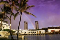Colourful dusk at a Hawaiin harbor. With a distant rainbow Stock Image